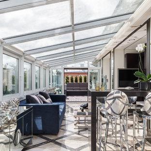 Modern inredning av ett stort uterum, med glastak, beiget golv och marmorgolv