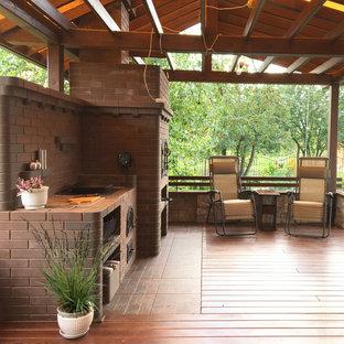 На фото: с высоким бюджетом перголы на террасе среднего размера на боковом дворе в современном стиле с летней кухней