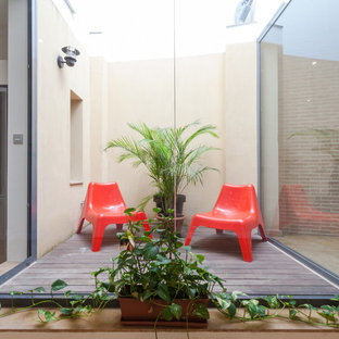 Design ideas for a small urban terrace in Seville with a potted garden and no cover.