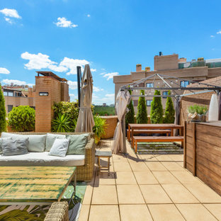 Photo of a large eclectic rooftop deck in Madrid with with privacy feature.