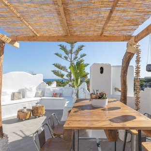 This is an example of a medium sized mediterranean roof terrace and balcony in Malaga with a potted garden and a pergola.