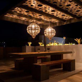 Example of a large trendy rooftop deck design in Malaga with a fireplace and a pergola