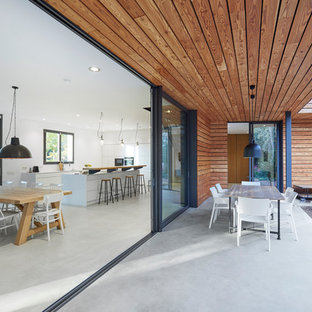 This is an example of a contemporary veranda in Other with concrete slabs and a roof extension.