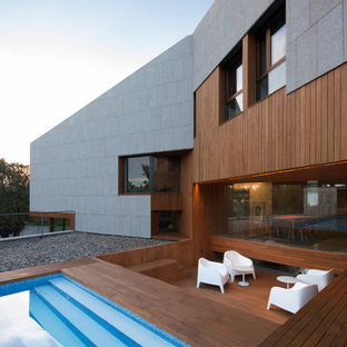 Expansive contemporary backyard deck in Madrid with a water feature and no cover.