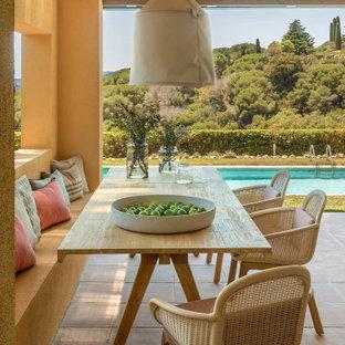 Ejemplo de terraza mediterránea, de tamaño medio, en patio trasero, con suelo de baldosas