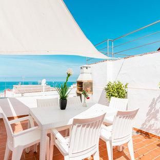 Ejemplo de terraza mediterránea, en azotea, con toldo