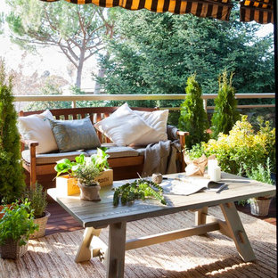 Inspiration for a small shabby-chic style deck container garden remodel in Barcelona with an awning
