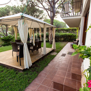 Modelo de terraza rústica, de tamaño medio, en patio delantero, con huerto