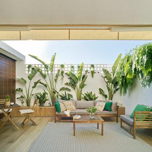 Imagen de terraza clásica, de tamaño medio, en patio trasero, con jardín vertical y toldo