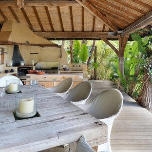 Inspiration pour un grand porche arrière ethnique avec un foyer extérieur et une pergola.