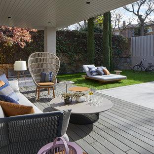 Diseño de terraza contemporánea en patio trasero y anexo de casas