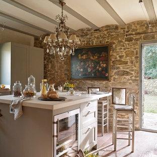 Inspiration för mellanstora lantliga linjära kök med öppen planlösning, med luckor med infälld panel, grå skåp, rostfria vitvaror, tegelgolv och en köksö