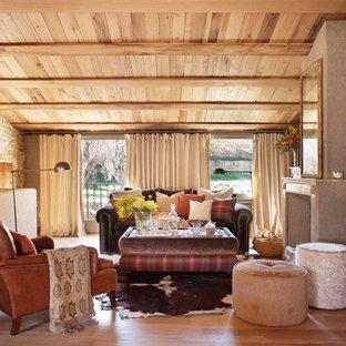 Imagen de sala de estar cerrada, rural, de tamaño medio, sin televisor, con suelo de madera en tonos medios, chimenea tradicional, paredes grises y marco de chimenea de piedra