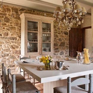バルセロナの中サイズのシャビーシック調のおしゃれなキッチン (落し込みパネル扉のキャビネット、グレーのキャビネット、レンガの床) の写真