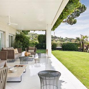 Ejemplo de terraza mediterránea, en patio trasero y anexo de casas, con suelo de baldosas
