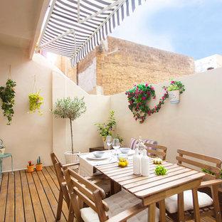 Diseño de terraza mediterránea, de tamaño medio, con jardín de macetas y toldo