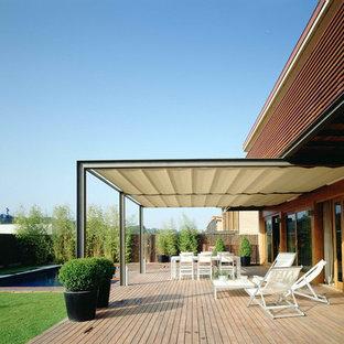 Imagen de terraza contemporánea, grande, en patio trasero, con toldo