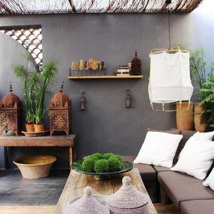 Foto de terraza ecléctica, de tamaño medio, en azotea, con jardín de macetas y toldo