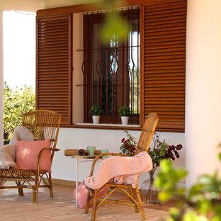 Diseño de terraza mediterránea, en patio delantero y anexo de casas, con suelo de baldosas