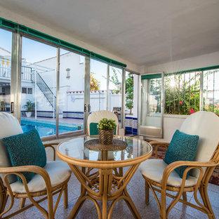 Imagen de porche cerrado mediterráneo, de tamaño medio, en patio trasero y anexo de casas, con suelo de baldosas
