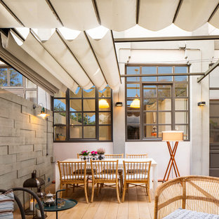 Inspiration for a medium sized industrial back terrace and balcony in Other with an awning.