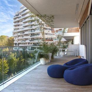 Immagine di terrazze e balconi design di medie dimensioni con un giardino in vaso e un tetto a sbalzo