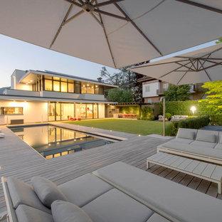 Ispirazione per una grande terrazza contemporanea dietro casa con un parasole