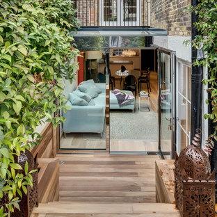 Bild på en liten funkis terrass på baksidan av huset, med en vertikal trädgård
