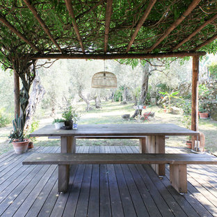 Inspiration for a mediterranean backyard deck in Milan with a pergola.