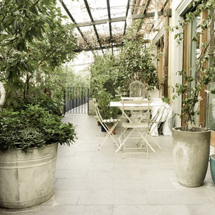 Deck - shabby-chic style side yard deck idea in Milan with a pergola