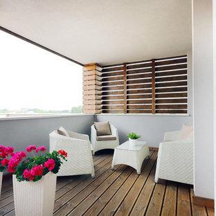 Ispirazione per una terrazza contemporanea con un giardino in vaso e un tetto a sbalzo