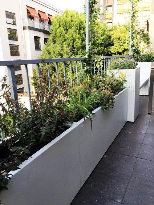 Terrazzo con fioriere, panca e arredi per una famiglia a Milano