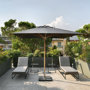 Inspiration for an expansive contemporary rooftop deck in Other with a vertical garden and an awning.