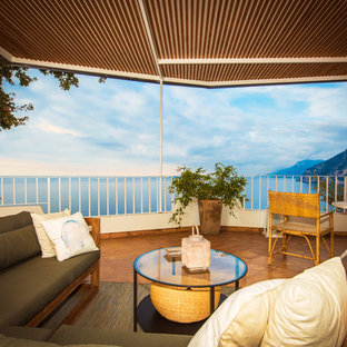 Esempio di terrazze e balconi mediterranei di medie dimensioni con un tetto a sbalzo