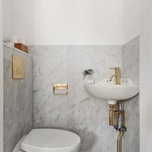 Immagine di un grande bagno di servizio scandinavo con WC sospeso, pareti bianche, pavimento in marmo e lavabo sospeso