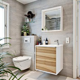 Bild på ett mellanstort tropiskt toalett, med en vägghängd toalettstol, vita väggar, mellanmörkt trägolv och ett väggmonterat handfat