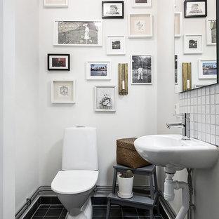 Foto på ett mellanstort nordiskt toalett, med en toalettstol med separat cisternkåpa, vita väggar, ett piedestal handfat, vit kakel, svart kakel, klinkergolv i keramik och svart golv