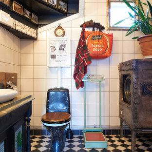 Foto på ett eklektiskt toalett, med skåp i shakerstil, en toalettstol med separat cisternkåpa, vit kakel och svart golv