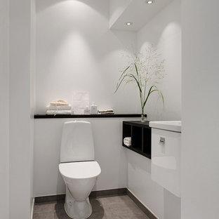 Idéer för ett mellanstort nordiskt toalett, med släta luckor, vita skåp, en toalettstol med separat cisternkåpa och grått golv