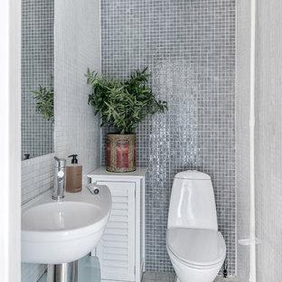 Foto på ett litet skandinaviskt badrum, med en toalettstol med hel cisternkåpa, grå kakel, mosaik, grå väggar, ett väggmonterat handfat och flerfärgat golv
