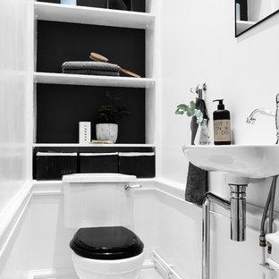 Exempel på ett litet klassiskt badrum, med öppna hyllor, en toalettstol med hel cisternkåpa, ett väggmonterat handfat, flerfärgat golv och svarta väggar
