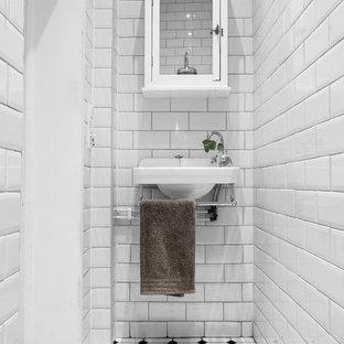 Inspiration för små nordiska toaletter, med vita skåp, vit kakel, vita väggar, ett väggmonterat handfat, tunnelbanekakel och flerfärgat golv