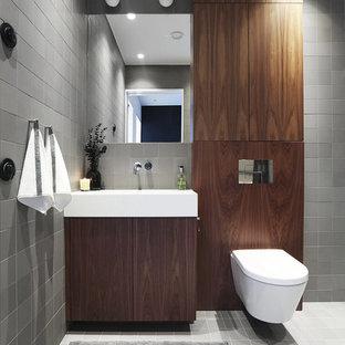 Inredning av ett modernt mellanstort toalett, med släta luckor, skåp i mörkt trä, en vägghängd toalettstol, grå kakel, grå väggar, ett integrerad handfat, keramikplattor, klinkergolv i keramik och grått golv