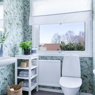 Modelo de aseo escandinavo, de tamaño medio, con armarios abiertos, sanitario de una pieza, paredes verdes, suelo de linóleo y suelo gris