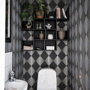 Exempel på ett minimalistiskt toalett, med en toalettstol med separat cisternkåpa, flerfärgade väggar, ett väggmonterat handfat och svart golv