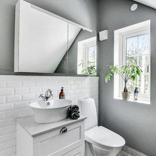 Inredning av ett skandinaviskt grå grått toalett, med skåp i shakerstil, vita skåp, vit kakel, tunnelbanekakel, grå väggar, ett fristående handfat och grått golv