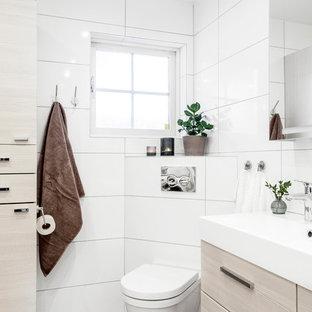 Inspiration pour un grand WC et toilettes nordique avec un placard à porte plane, des portes de placard en bois clair, un WC à poser, un carrelage blanc, des carreaux de porcelaine, un mur blanc, un sol en calcaire, un lavabo posé et un sol gris.