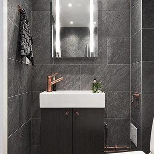 Exempel på ett litet modernt toalett, med släta luckor, svarta skåp, svarta väggar, klinkergolv i keramik, en toalettstol med separat cisternkåpa, ett integrerad handfat, grå kakel, grått golv och skifferkakel