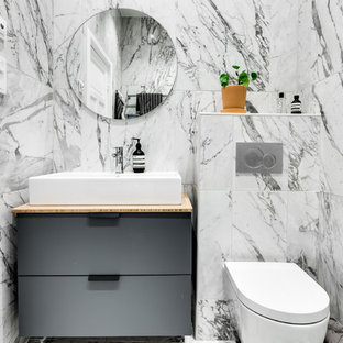 Inspiration for a small scandi cloakroom in Stockholm with flat-panel cabinets, grey cabinets, a wall mounted toilet, grey tiles, white tiles, multi-coloured tiles, a vessel sink, wooden worktops and beige worktops.