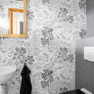 Inspiration för ett funkis toalett, med en vägghängd toalettstol, svart kakel, ett väggmonterat handfat och svart golv